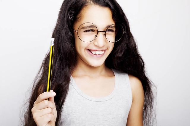 一个美丽的非洲孩子女孩在眼镜手拿铅笔.jpg